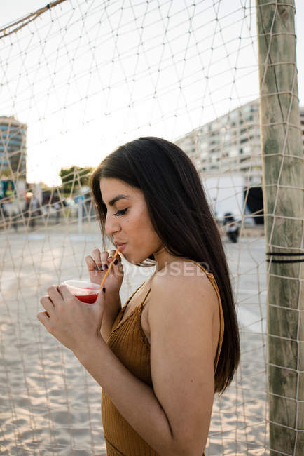 Young adult woman with long hair drinking lemonade on sandy shore — Stock Photo