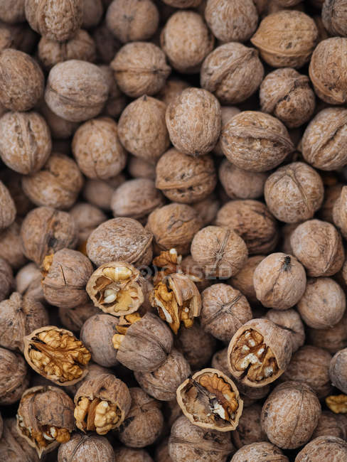 Close-up of whole and cracked walnuts in heap — Stock Photo