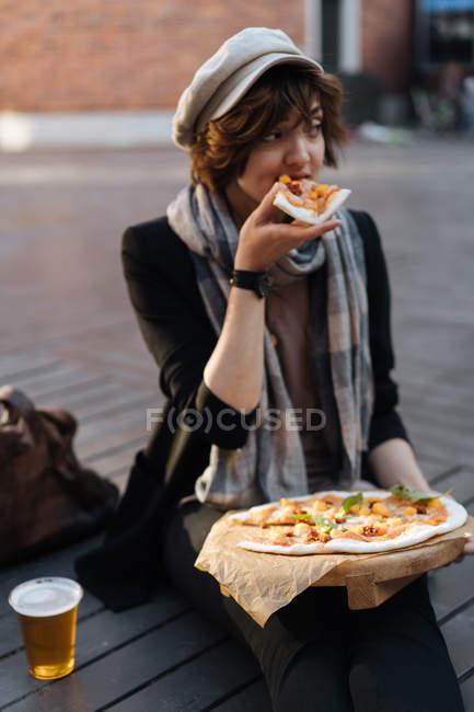 Молодая женщина сидит на подиуме на улице со стаканом пива и ест пиццу — стоковое фото