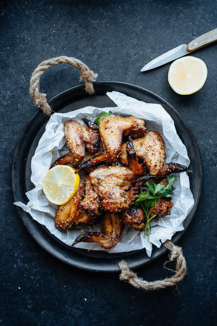 Baking dish of baked chicken wings in sesame and parsley with lemon — Stock Photo
