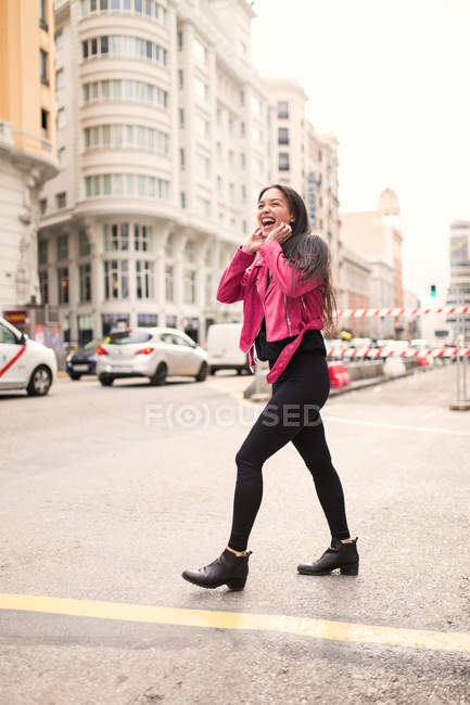 Trendy young woman in pink jacket walking on street and laughing — Stock Photo