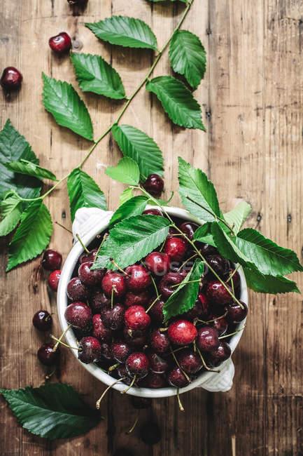 Piatto laici della ciotola di ceramica riempito con ciliegie e composto con foglie verdi sulla tavola rustica — Foto stock