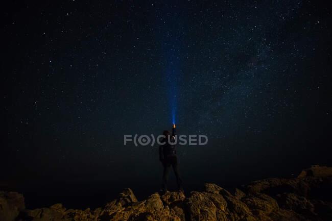 El hombre encendiendo al hombre brillando una linterna a las estrellas en la noche por la noche - foto de stock