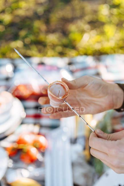 Mani umane organizzando strisce di pancetta piegata sullo spiedo in metallo per pasto barbecue — Foto stock