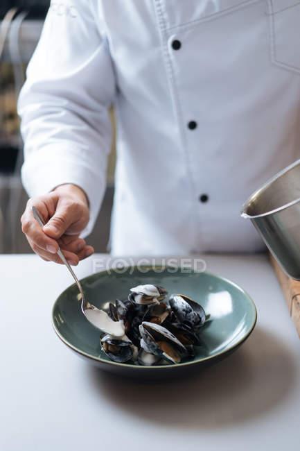 Шеф-повар, гарнировать блюдо северных из морепродуктов с мидиями и сливочным соусом на плите — стоковое фото