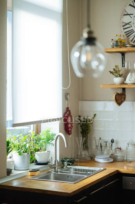 Легкий дерев'яний кухонний інтер'єр з раковиною, плитою і дерев'яними різальними дошками з кошиком та іншим посуду з начинкою на сітку. — стокове фото
