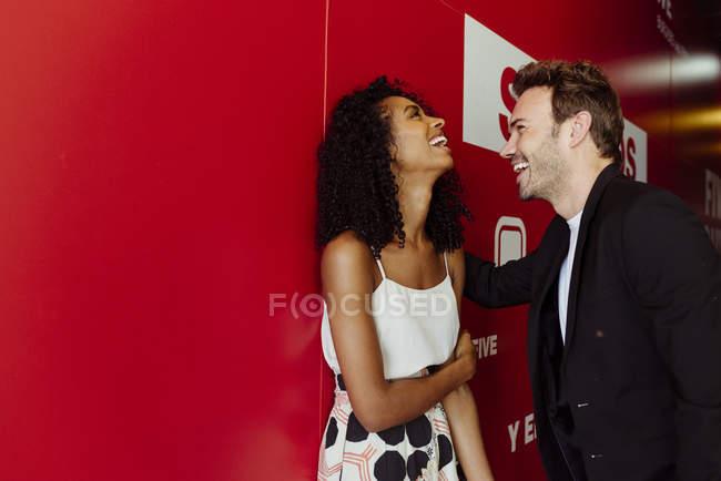 Bonito homem apoiando-se na parede vermelha e flertando com a mulher afro-americana no corredor de construção — Fotografia de Stock