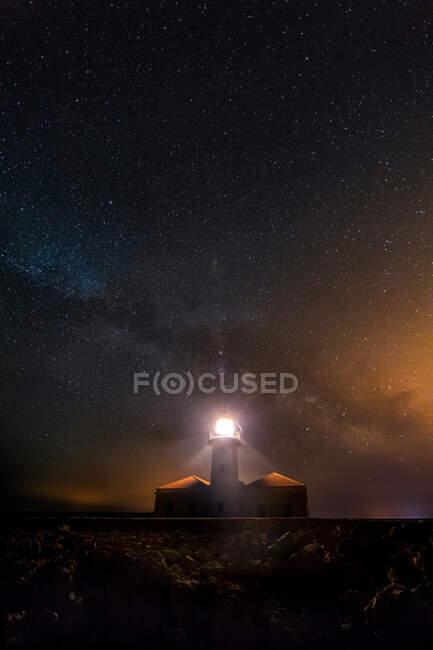 Lighthouse shining in the night of stars. Cavalleria, Menorca, Spain — Stock Photo