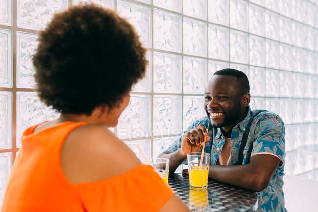 Seitenansicht des schwarzen Mann und Frau lächelnd und sahen einander am Café-Tisch sitzen und mit Getränken — Stockfoto