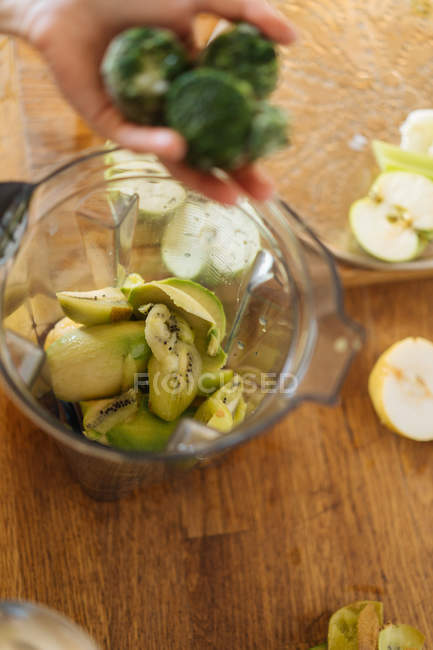 Human hand putting ingredients into plastic cup of blender filled with fruit and vegetable mix for smoothie — Stock Photo