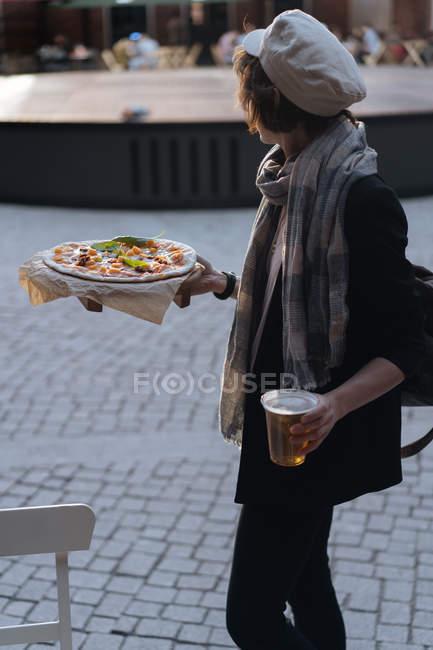 Женщина держит стакан пива и пиццу во время прогулки в кафетерии на улице — стоковое фото