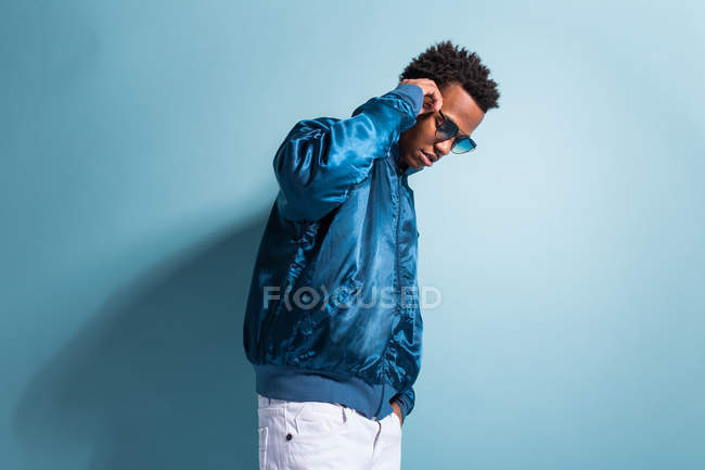 Cool black man in blue outfit and sunglasses standing on blue background — Stock Photo