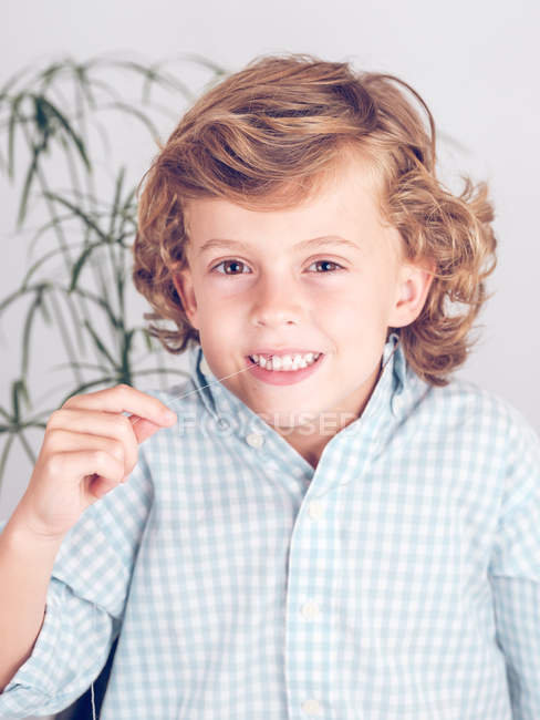 Boy in shirt pulling tooth out with thread while looking at camera — Stock Photo