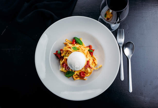 Pasta fettuccine with meat, potherbs and goat cheese sphere on white plate — Stock Photo