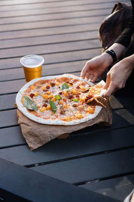Женщина сидит на улице со стаканом пива и печет вкусную пиццу — стоковое фото