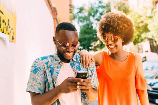 Uomo afroamericano divertente e donna che ride e navigazione smartphone moderno mentre levandosi in piedi sulla strada — Foto stock