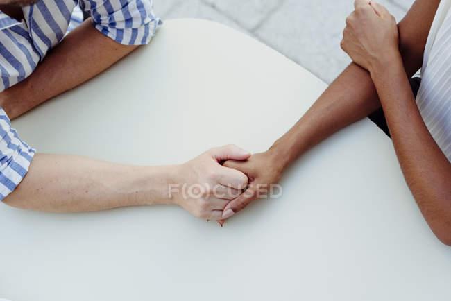 Unbekanntes Paar hält Händchen, während es gemeinsam am Tisch im Café sitzt — Stockfoto