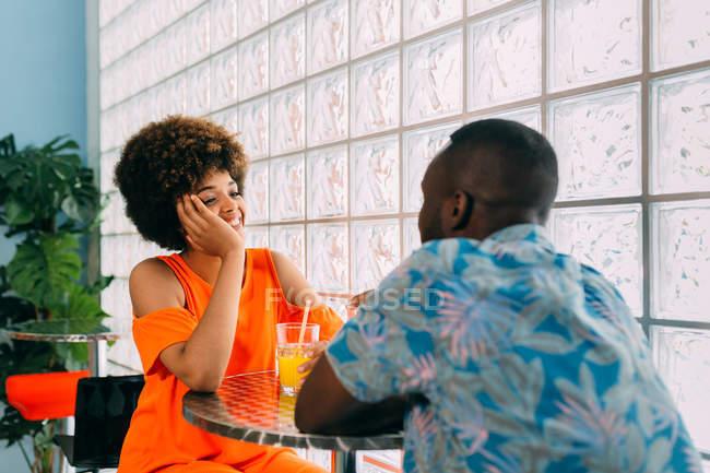 Seitenansicht des schwarzen Mann und Frau lächelnd und sahen einander am Café-Tisch sitzen und Getränk — Stockfoto