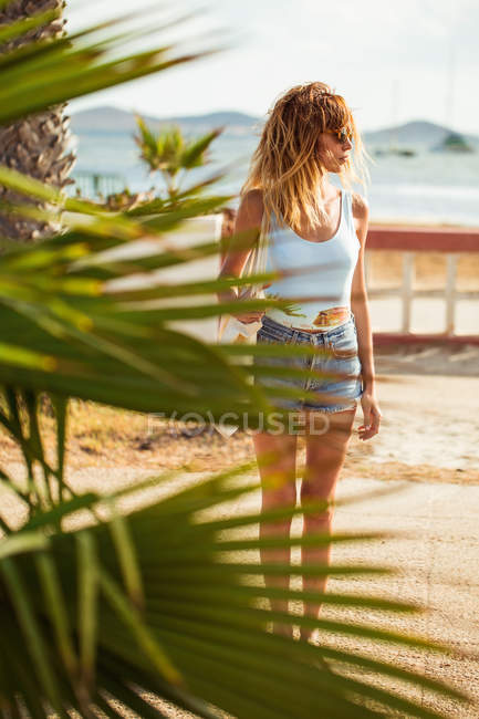 Woman in swimsuit and denim shorts looking away on coast — Stock Photo