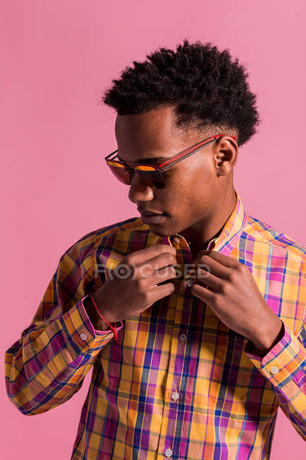 Young African American man in trendy multicolored checkered shirt and sunglasses standing on pink background — Stock Photo