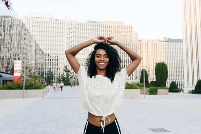 Смеющаяся афроамериканка, стоящая на улице с поднятыми руками и смотрящая в камеру — стоковое фото