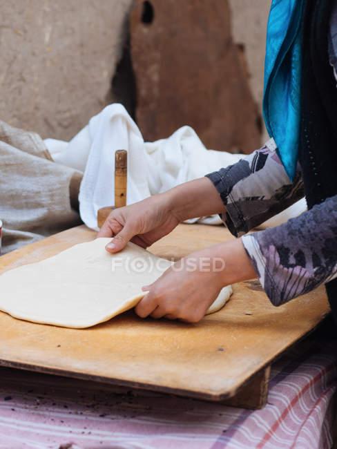 Mains féminines rouler la feuille de pâte sur une planche de bois — Photo de stock