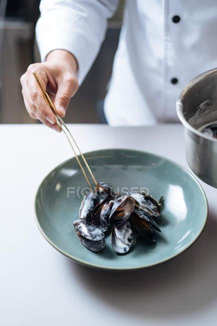 Шеф-повар блюдо северных морепродуктов с мидиями на тарелке крупным планом — стоковое фото