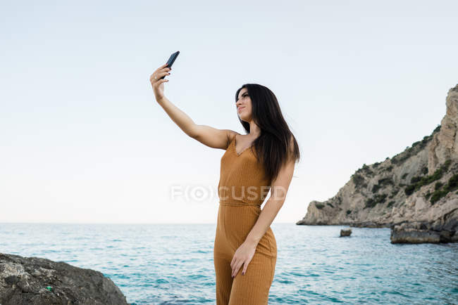 Trendy brunette in fashionable overall taking selfie on cliff of seascape — Stock Photo