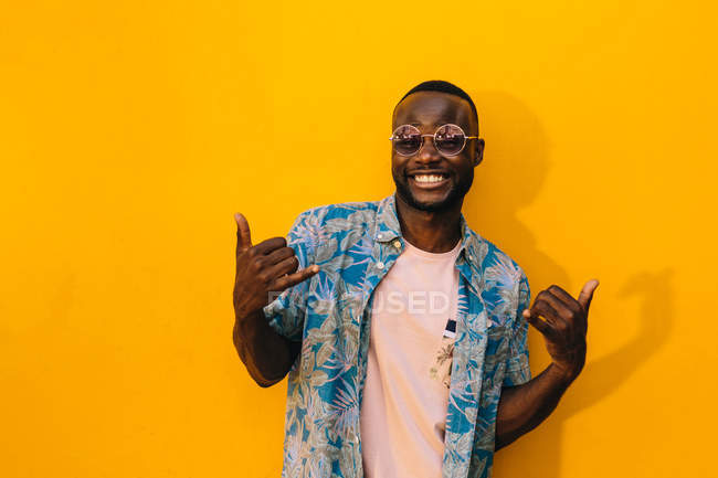 Handsome African American man with shaka gesture smiling while standing against bright yellow background — Stock Photo