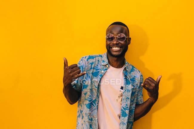 Bonito homem afro-americano com gesto de shaka, sorrindo em pé contra fundo amarelo brilhante — Fotografia de Stock