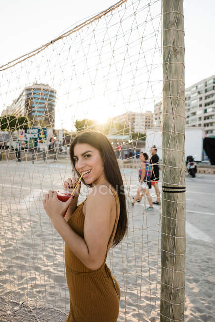 Playful young woman enjoying drink on beach — Stock Photo