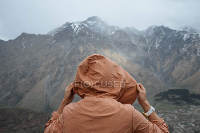 Back view of male in warm clothes with backpack hiking in mountains standing on grass looking at jagged mountain ridge covered with snow and peaks hidden in clouds — Stock Photo