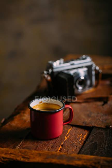 Emaille-Tasse Kaffee auf rustikaler Holzoberfläche mit Retro-Kamera — Stockfoto