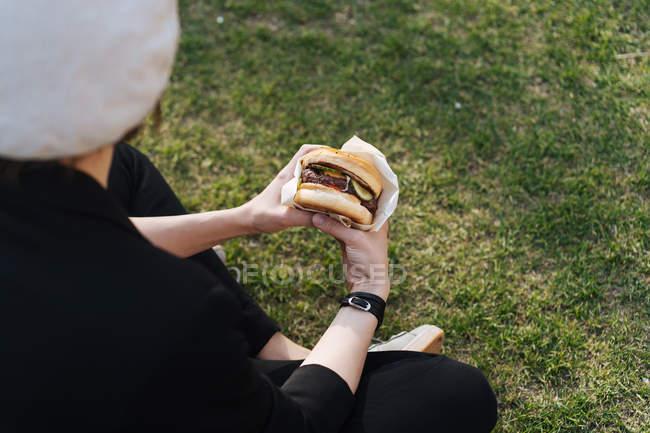 Стильная женщина сидит на траве парка и держит вкусный бургер на вынос — стоковое фото