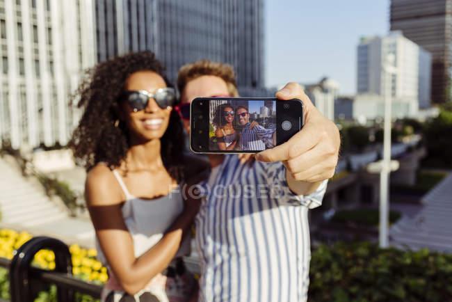 Joyeux couple multiracial posant pour selfie lorsque vous êtes debout sur fond de ville moderne — Photo de stock