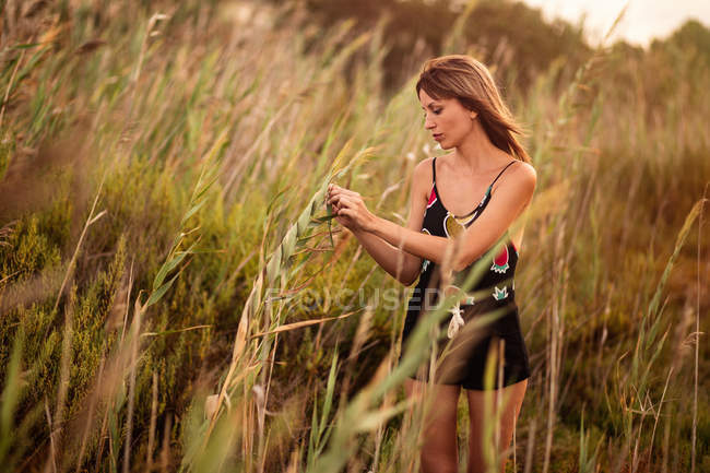Woman in summer outfit standing in field grass — Stock Photo