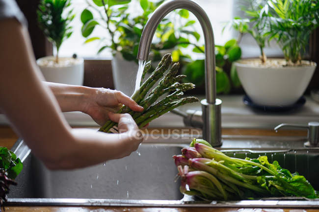 Female hands washing fresh green asparagus in kitchen sink — Stock Photo