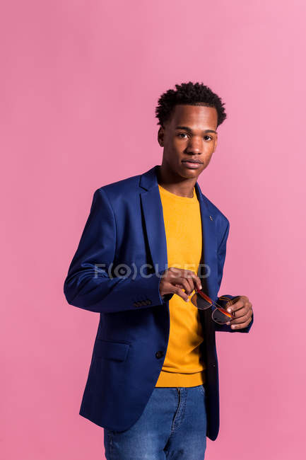 Portrait of Dandy black man in jacket holding sunglasses on pink background — Stock Photo