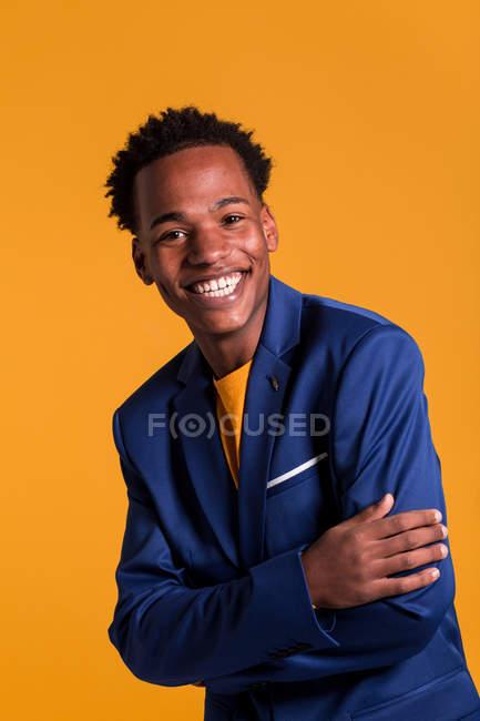 Portrait de dandy homme noir veste sur fond orange souriant — Photo de stock