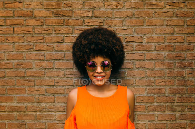 Attractive African American woman in stylish sunglasses smiling and looking in camera while standing near brick wall — Stock Photo