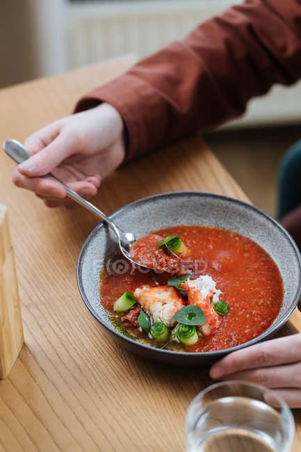 Человек ест традиционный нордический красный суп, украшенный травами — стоковое фото