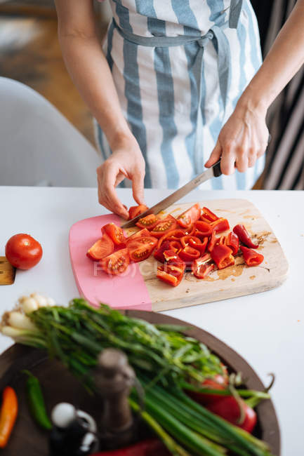 Female hands cutting red peppers and tomatoes on chopping board — Stock Photo