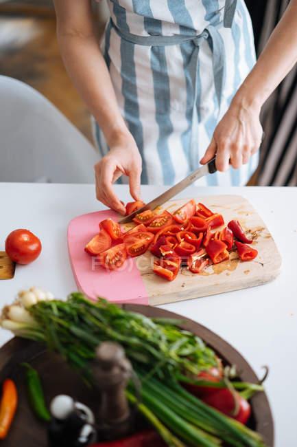Жінка тримає різання червоний перець і помідори на Розробні рада — стокове фото