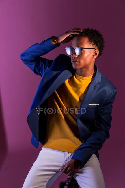 Stylish modern black man in lamplight on purple background — Stock Photo