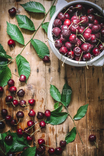 З плоским закласти керамічні чаші наповнені вишні і складається із зеленим листям на сільському стилі таблиці — стокове фото