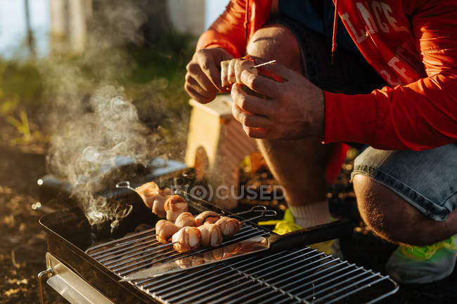 Male hands preparing bacon and sausages on skewers grilling on burning charcoal in portable griddle outdoors — Stock Photo
