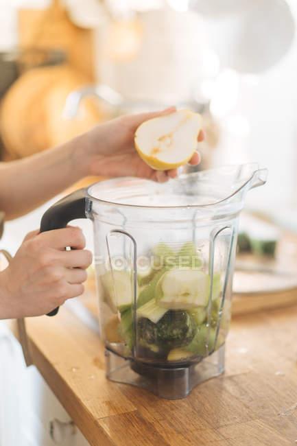 Mujer manos pera poner en un tazón licuadora de batidos verdes - foto de stock