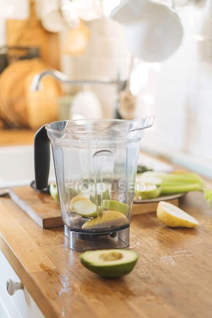 Vaso de plástico de blender con aguacate y pera para batido de cocina madera - foto de stock