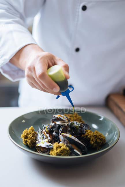 Шеф-повар, капает с соус блюдо северных морепродуктов с мидиями на плите — стоковое фото