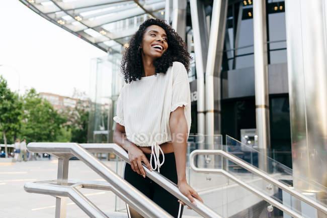 Mujer afroamericana riendo de pie cerca de la barandilla de la escalera en la calle de la ciudad - foto de stock